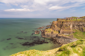 Early morning sunlight over Dunluce Castle at the Causeway Coast of Northern Ireland