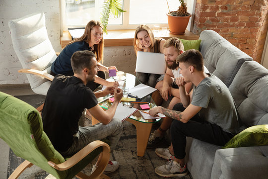 Group of young caucasian office workers meeting to discuss new ideas. Creative meeting. Teamwork and brainstorming. Men and women meet in office to plan their future working. Business concept.