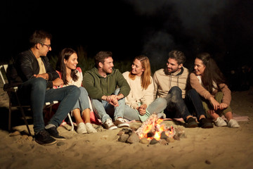 leisure and people concept - group of smiling friends sitting at camp fire on beach at night