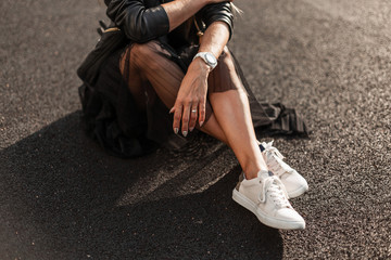 Young woman in stylish white sneakers in a vintage black skirt in a trendy leather black skirt sits on the asphalt on a sunny day. Fashionable autumn collection of youth women's clothing. Close-up.