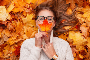 Top view on a positive young woman in stylish glasses in an knitted white sweater with an orange leaf near face in the park on a background of golden foliage. Joyful happy girl lies in the forest. Wall mural