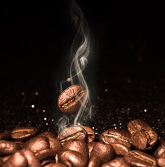 Foto op Plexiglas Cafe Roasted coffee beans. Seeds of freshly roasted coffee with smoke. Coffee beans closeup with emphasis on the grain with smoke.