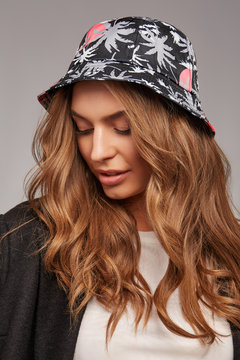 Medium close-up shot of a charming blonde European lady with wavy hair dressed in a beige top, a black jacket and a black bucket hat with gray palms print.