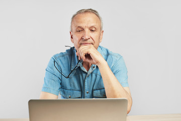 Elderly Caucasian man in glasses with a serious expression on his face working on a laptop at his desk on a white background