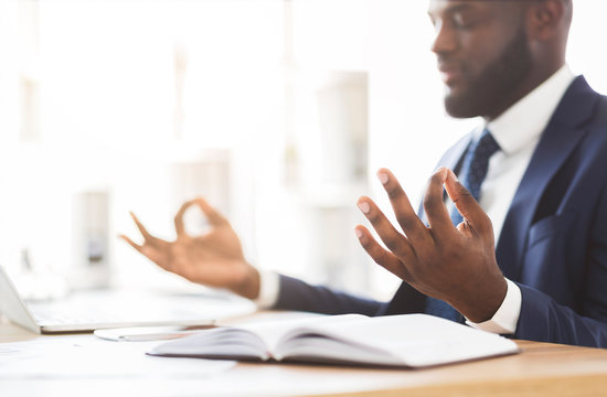 Cropped image of businessman meditating in office during working day