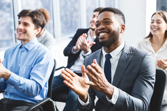 Happy businessmen applauding good presentation in office