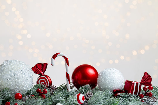 Christmas white and red composition with globes, sweets, candy cane and lollypop over some snowy fir or pine branches with cones. light bokeh background and copy space.