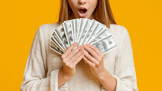 Amazed young woman holding bunch of money banknotes, celebrating profit