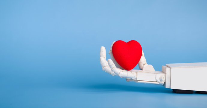 Medical robotics and science fiction concept. Robot hand holding red heart