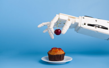 Robot hand putting fresh cherry on top of the cupcake