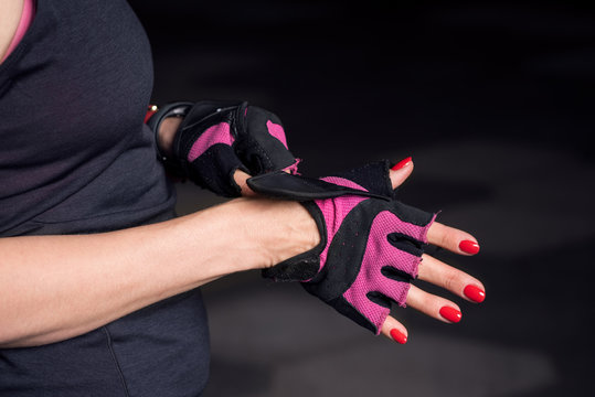 Closeup of woman putting on workout gloves with no brand logo over manicured hands with bright red nail polish on black background