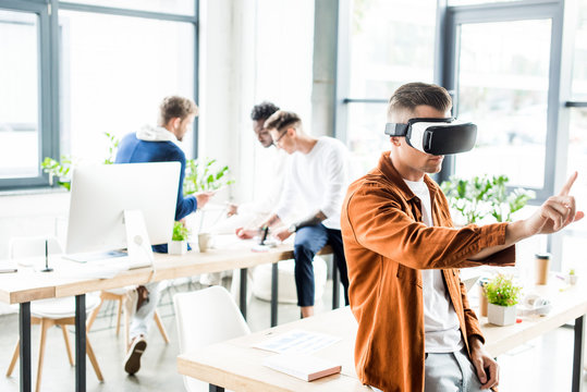 young businessman using vr headset and touching something with finger while multicultural colleagues working in office