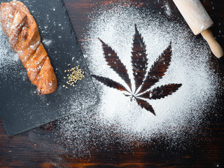 cooking cannabis food. Trail of cannabis leaf on white flour. on a wooden table