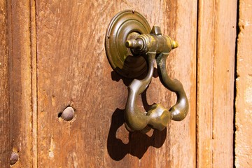 Close up of antique metal iron door knocker on old wood entrance in bright natural sun light - Provence, France