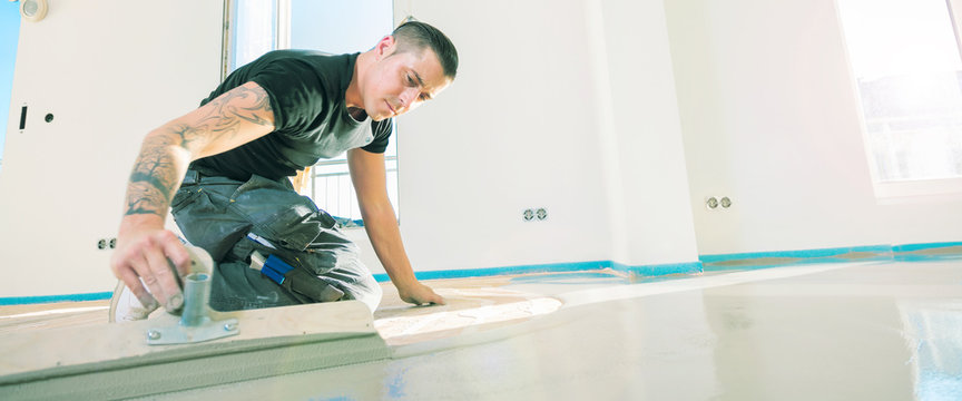 male worker working with self-levelling cement mortar during floor renovation