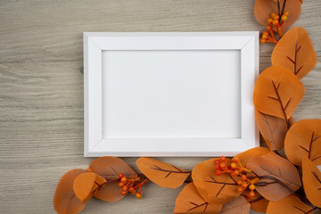 white picture frame decorated with orange berries on wooden table, top view