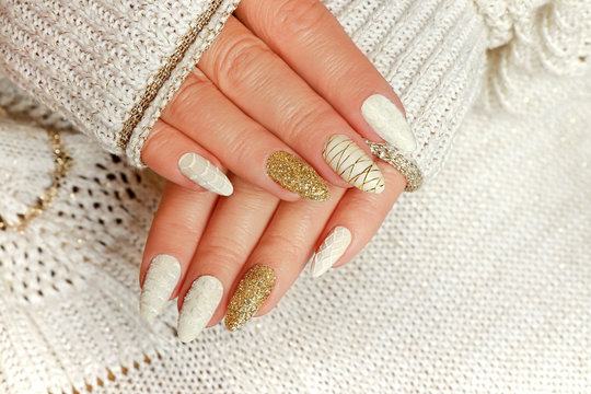 Knitted sand manicure on long oval nails with golden sequins and threads on the female red in a jacket. Winter trend in nail design.
