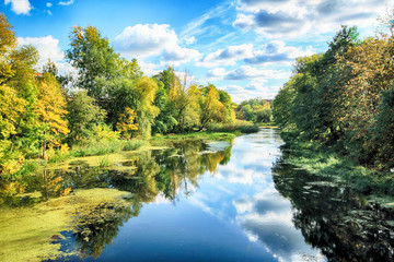 WROCLAW, POLAND - OCTOBER 06, 2019: Olawa River in Wroclaw, Poland. Beautiful autumn landscape on a sunny day. Wild, untouched nature in the city.
