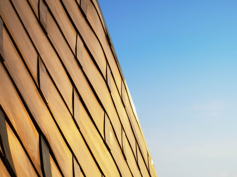 View of metal copper building, Curve architectural design, Abstract facade of architecture skin on blue sky background.