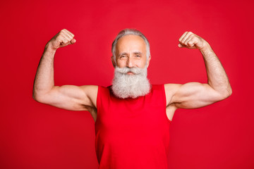 Portrait of cool powerful santa claus looking proud show biceps smile wearing sports wear isolated over red background
