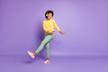 Full length body size photo of cheerful wavy curly haired sweet pretty girl of freedom wearing green pants trousers dancing listening to her music out of headphones isolated over violet color pastel