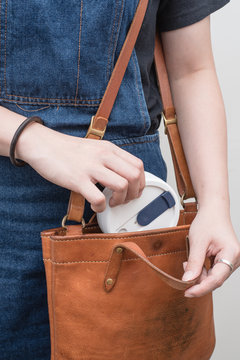 Young woman taking out/storing a silicone collapsible cup, reusable coffee tumbler from/into her handbag.