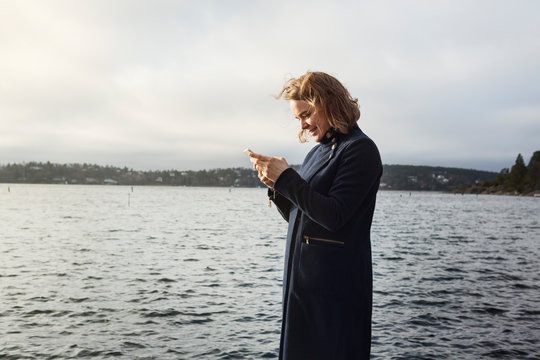 Young woman standing next to lake holding cell phone