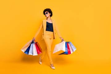 Full size photo of positive cheerful girl have leisure time feel dream dreamy hold bags go from shopping center wear style blazer trousers stilettos isolated over yellow color background