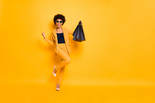 Yeah 50-off. Full size photo of crazy curly hair girl has shopped raise fists scream hold black bags celebrate bargain sales wear blazer pants high-heels isolated bright color background