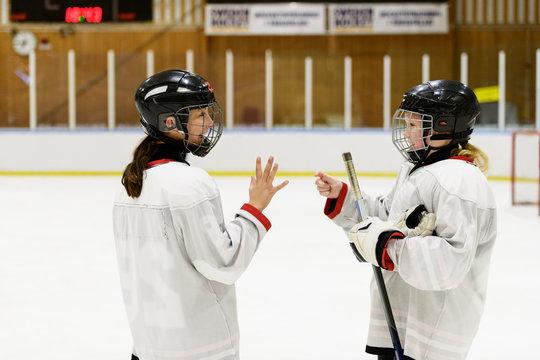 Girls on ice rink for ice hockey training