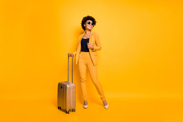 Full size photo of positive cheerful girl hold trolley package ready to enjoy free time on vacation wear stylish fashionable outfit pants footwear isolated over yellow color background