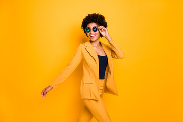 Profile side photo of charming positive cheerful dark skin lady touch her eyeglasses have free time go walk wear stylish clothes isolated over yellow bright color background