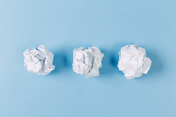 Crumpled paper balls, waste and recycling concept on blue background