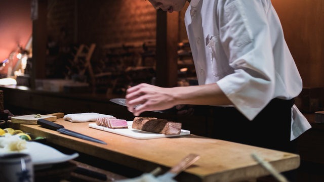 Chef preparing slicing fish, otoro. Omakase style Japanese traditional.