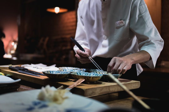 Chef preparing food with chopsticks. Omakase style Japanese traditional.
