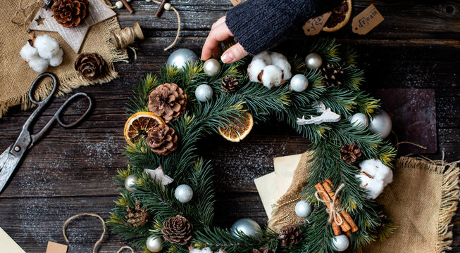 overhead shot of handmade christmas wreath with grey balls, pine cones, dried orange slices, cinnamon sticks in woman hand on rustic wooden table with old scissors, sackcloth, new year toys