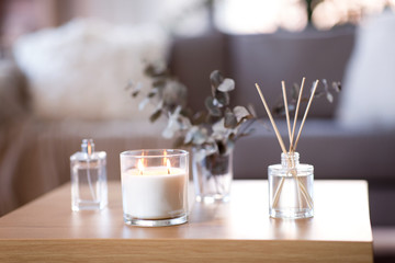 Obraz decoration, hygge and aromatherapy concept - aroma reed diffuser, burning candle, branches of eucalyptus populus and perfume on table at home - fototapety do salonu