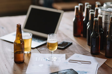 Beer bottle, glasses, documents and laptop on table