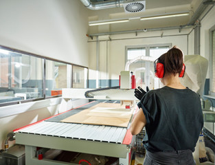 Rear view of woman at CNC machine in workshop