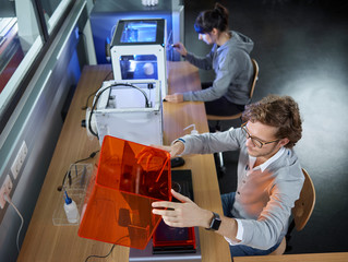 Two technicians sitting at table with 3D printer