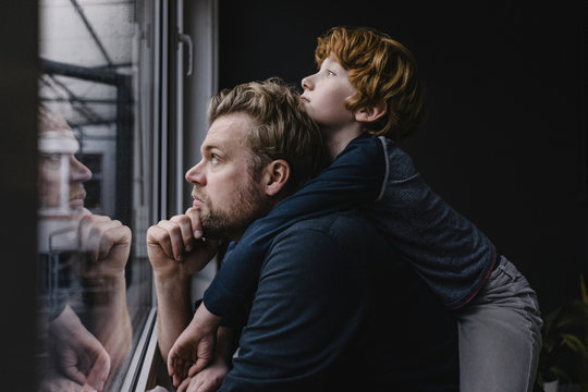 Side view of father and son looking through window