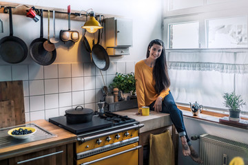 Portrait of smiling young woman sitting on kitchen counter at home