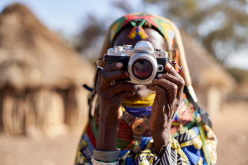 Muhila traditional woman taking pictures with a camera, Kehamba, Chibia, Angola