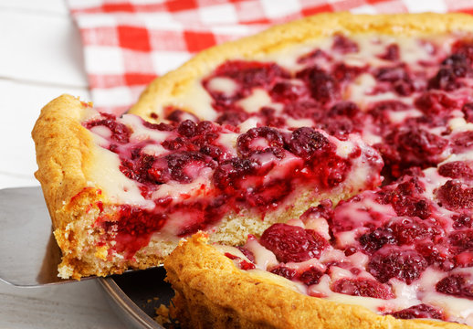 Closeup homemade raspberry pie with yogurt filling and piece cut of. Shallow focus.