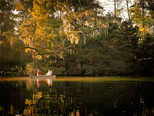 Men looking relaxed while fishing together in a boat on a lake.