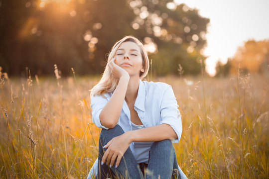 Young woman sitting on dry grass under sunlight. Eyes closed