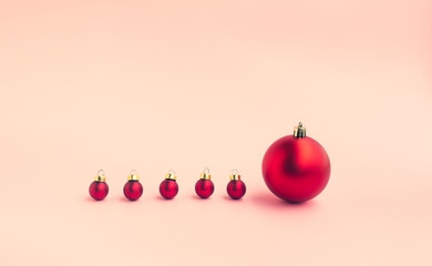 Christmas festival concepts ideas with difference size of red ball ornament on pastel color background.