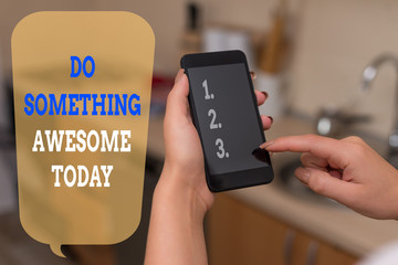 Writing note showing Do Something Awesome Today. Business concept for Make an incredible action motivate yourself woman using smartphone and technological devices inside the home