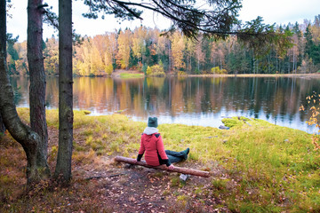 young woman sits on a lake and admires nature and vibrant forest during golden autumn