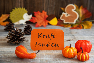 Orange Label With German Text Kraft Tanken Means Relax. Autumn Decoration Like Pumpkin, Hedgehog And Squirrel